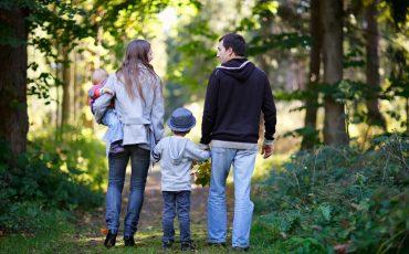 Familj på promenad i skogen