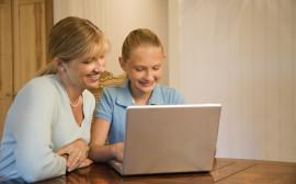 Två kvinnor vid en dator, kanske en mamma och dotter