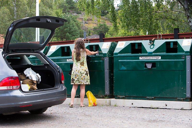 Tjej slänger sopor i återvinningscontainer