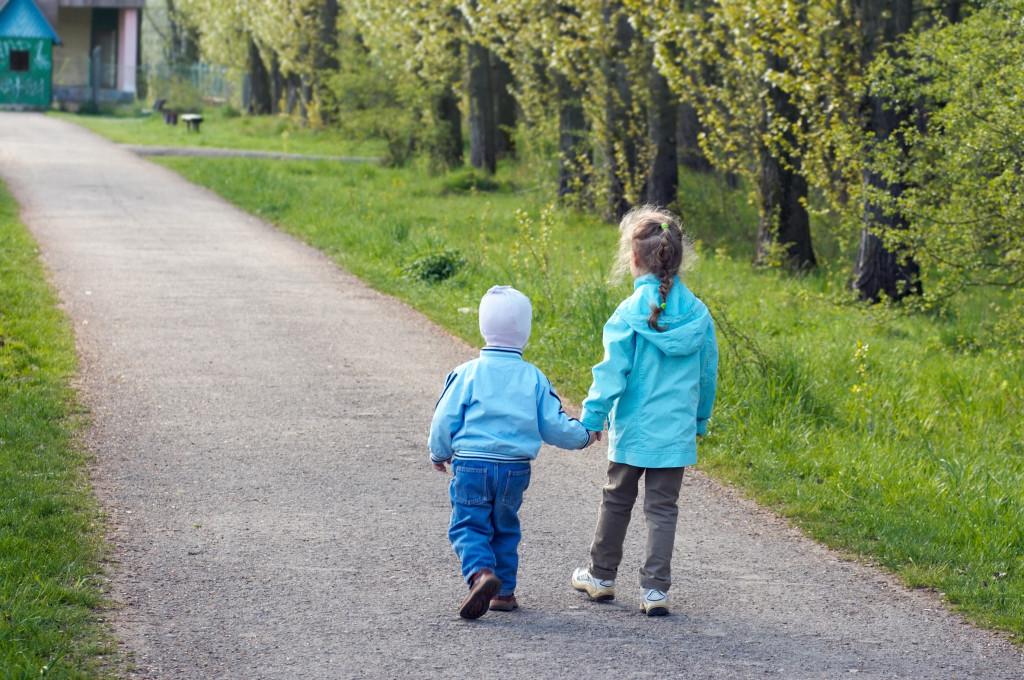 Två barn hand i hand på promenad