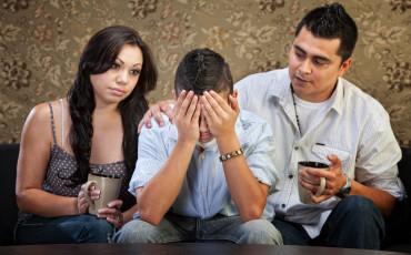 Ledsen ungdom tillsammans med föräldrarna