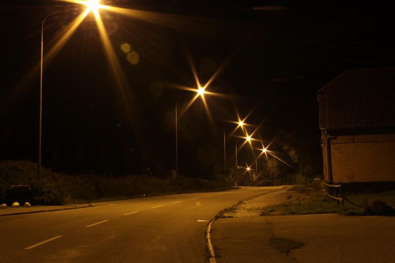 Gatubelysning som lyser i mörkret längs med en gata