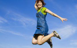 Glad tjej som hoppar högt