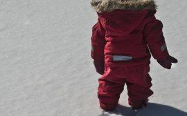 Barn som går i snön