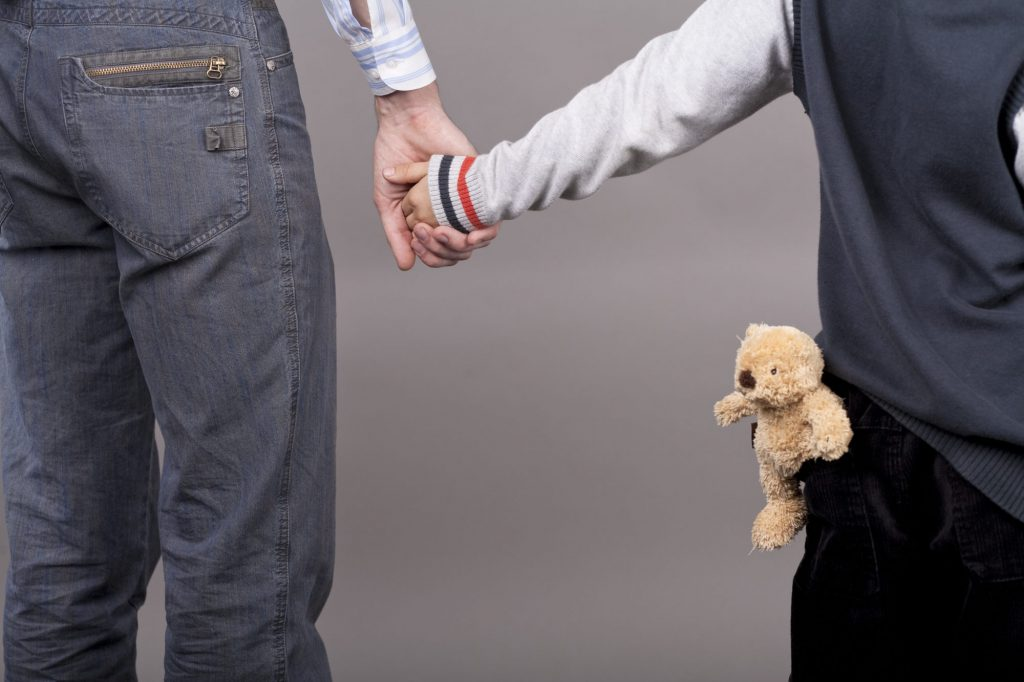 pappa och barn hand i hand med nalle i fickan