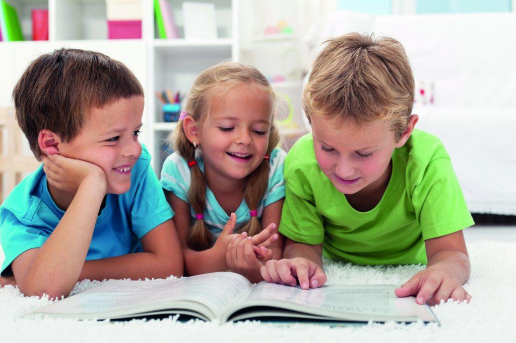 Tre barn ligger på mage och läser