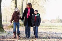 Mamma med två barn är ute på promenad