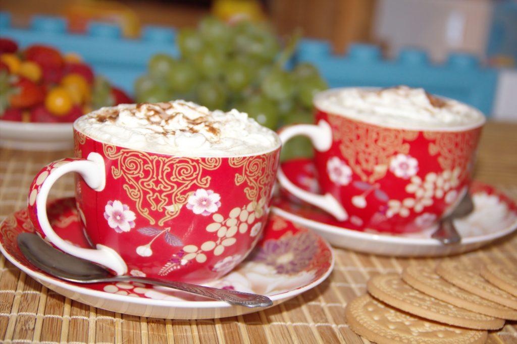 Två kaffekoppar toppade med vispad grädde