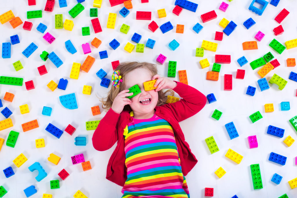 Barn som ligger på golvet med en massa färgade legobitar