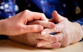 En ung hand håller i en äldre persons händer