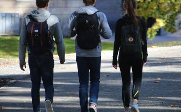 Tre ungdomar som går.