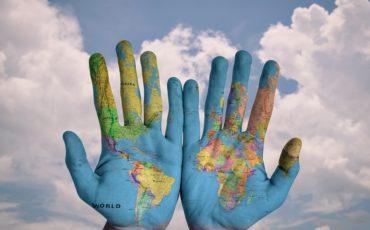 Händer som har jorden målad på handflatorna men himlen som bakgrund