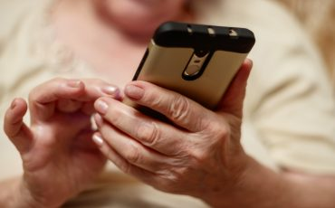 Äldre kvinnas händer och en mobiltelefon