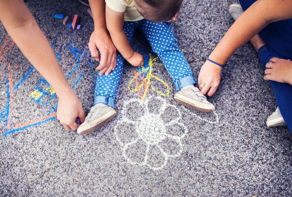 Barn och vuxna målar på marken