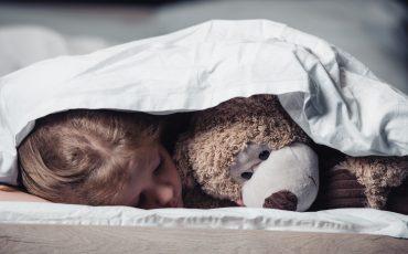 barn och en nalle i sängen