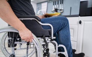 Man sitter i rullstol i ett kök