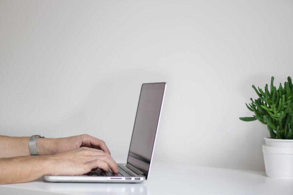 Händer skriver på ett tangentbord till en dator