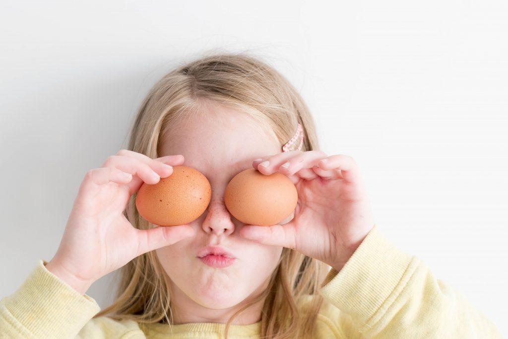 Flicka med ägg för ögonen