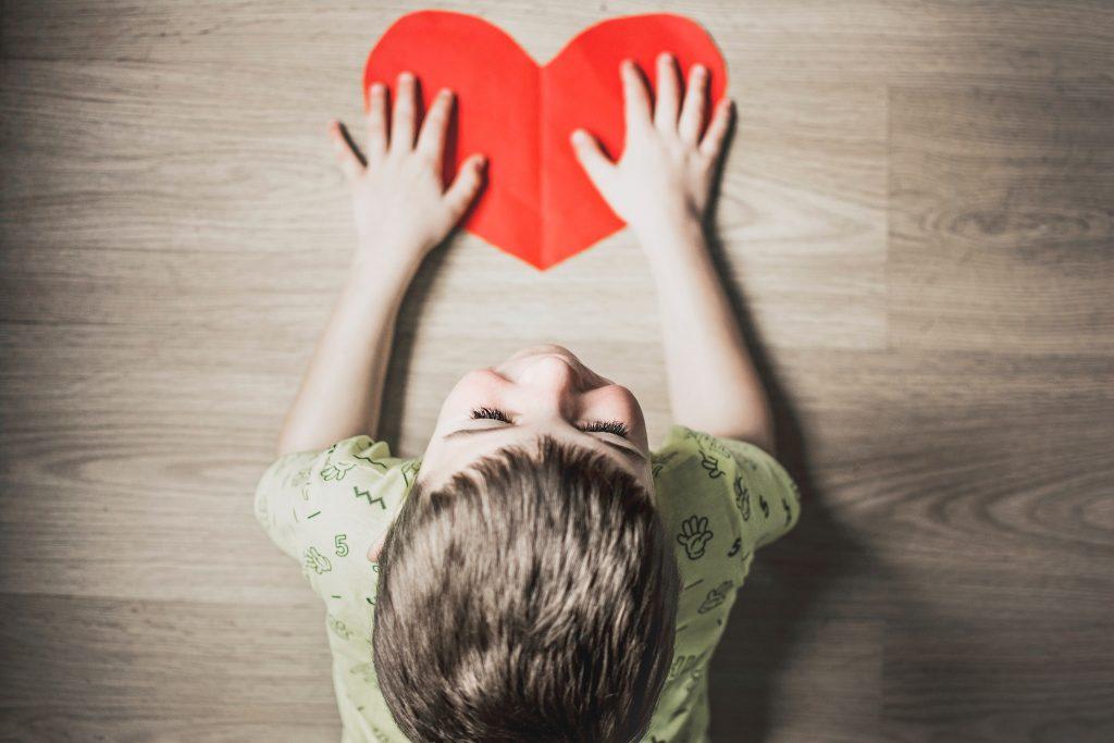 Pojke och ett rött pappershjärta