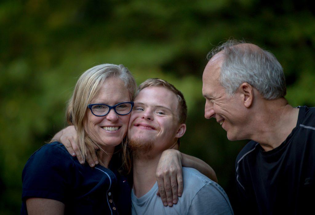 En kvinna och en äldre pojke håller armarna om varandra. En man står intill och tittar på.