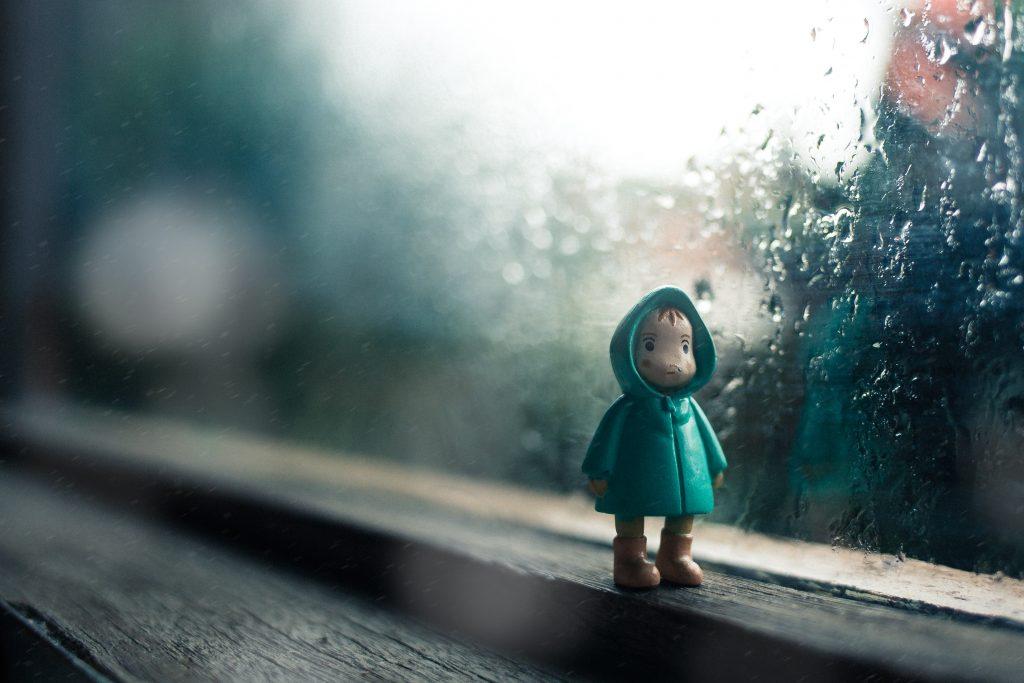 leksaksfigur framför fönster som det regnar på