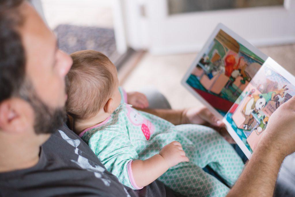 man läser bok för bebis