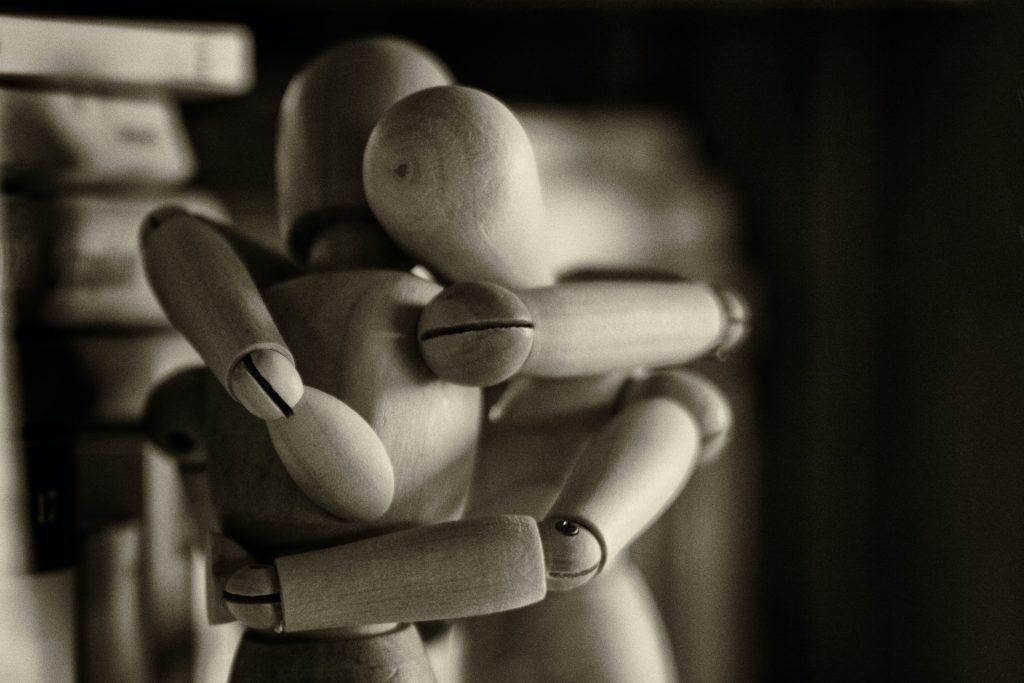 träskulpturer av människor som kramas