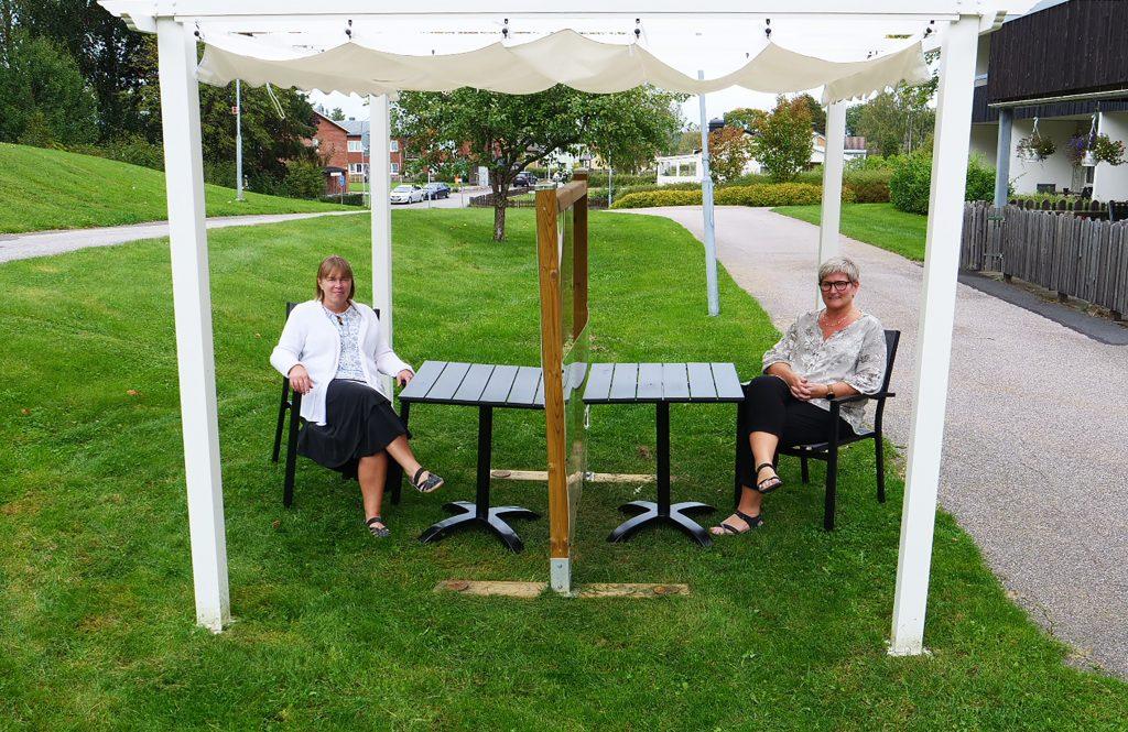 Två kvinnor vid ett bord med plexiglasskiva
