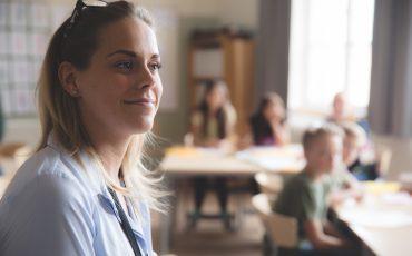 Kvinna i förgrunden. Skolelever i bakgrunden.