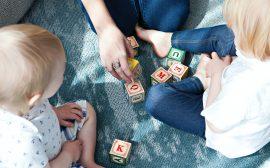 Barn som sitter på golvet.