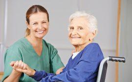 Kvinna i rullstol med vårdpersonal bredvid