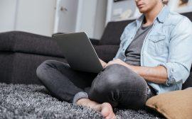 Kille som sitter med sin dator i knät