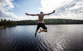 Kille hoppar i en sjö